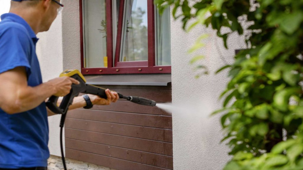 Man Pressure Washing Exterior Of House - House Pressure Washing