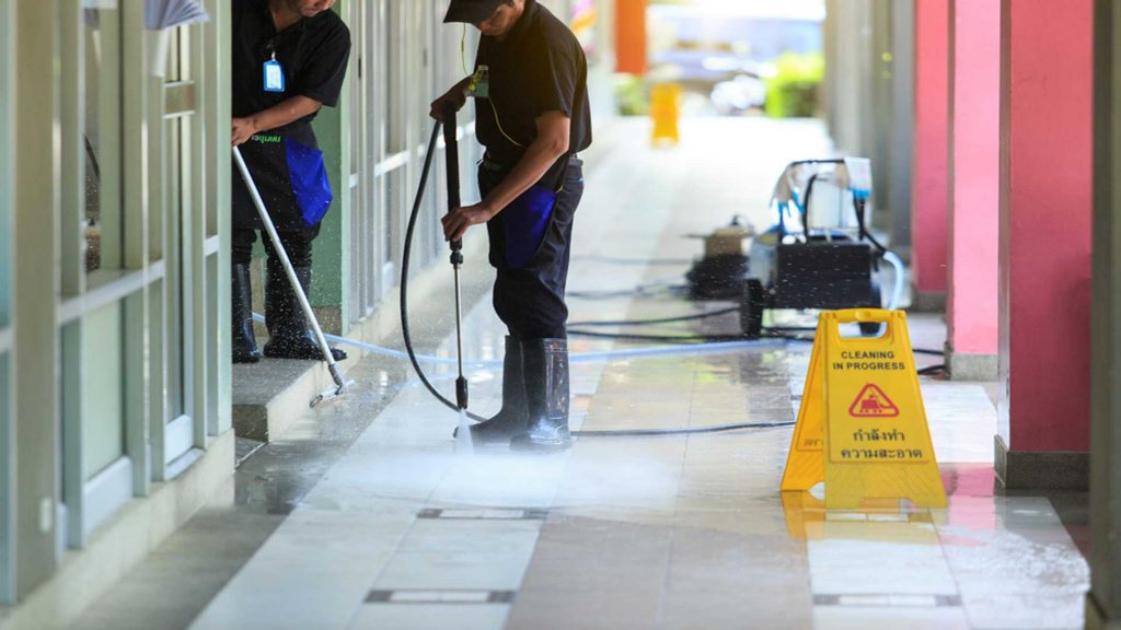 Two Men Power Washing A Store Front - Commercial Pressure Washing